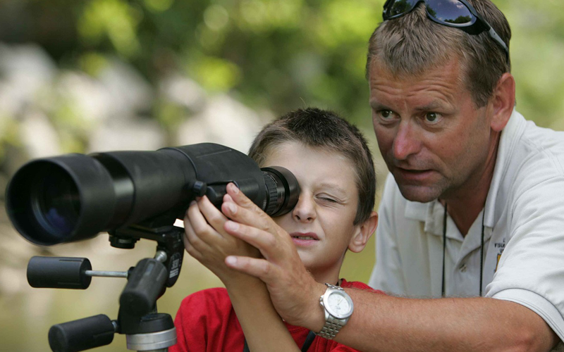a child using a spotting scope with his father