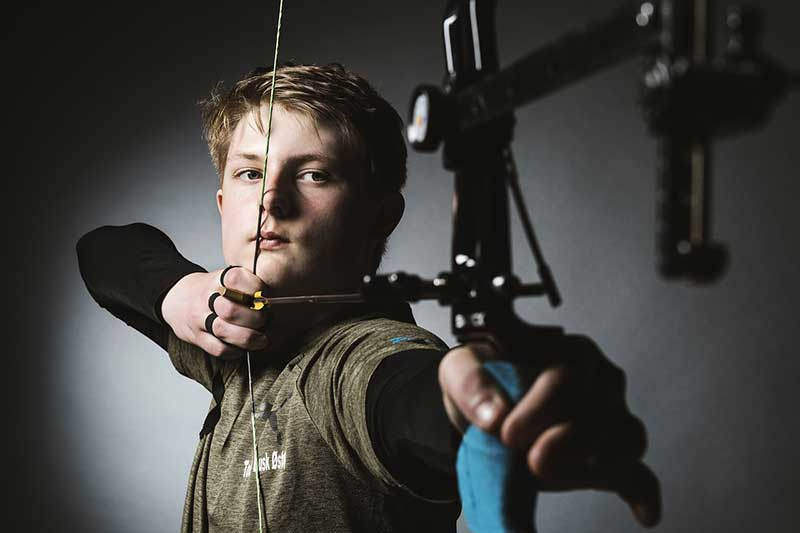 boy aiming used bow